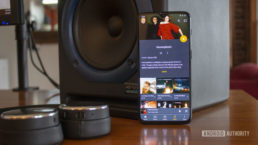 A smartphone leaning up against a speaker. The smartphone has the Plex music player on its display.